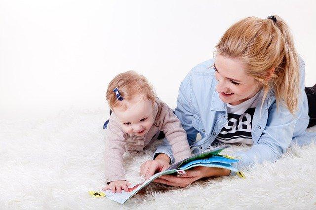 žena s dítětem, prohlíží knihu